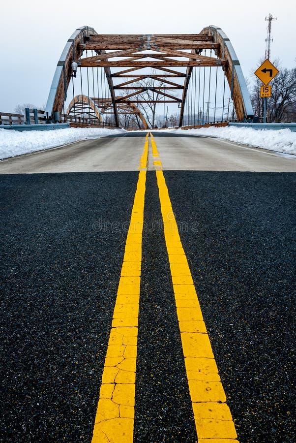 Roadway yellow lane leading to complex modern geometrical bridge stock photos