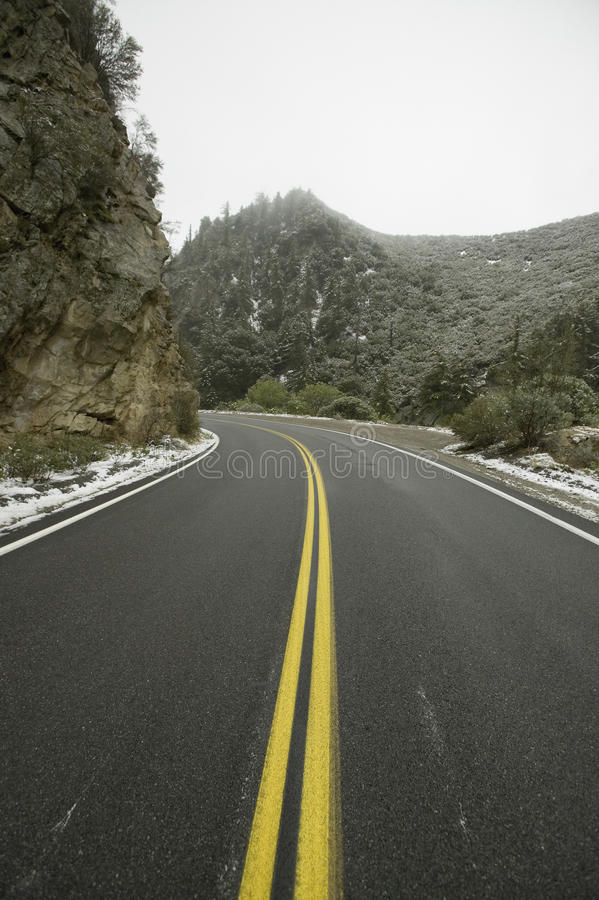 Roadway with yellow stripe. As it runs along a rocky cliff in the midst of snow storm in the high-desert of Lockwood Valley, Las Padres National Forest royalty free stock images