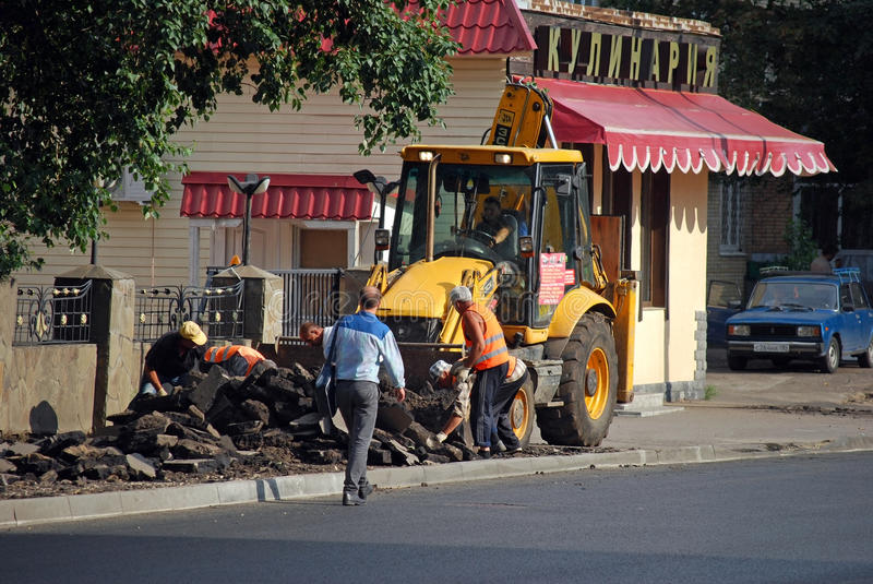 roadwork El tractor vierte el asfalto quitado después del viaje en el camión volquete imagen de archivo libre de regalías