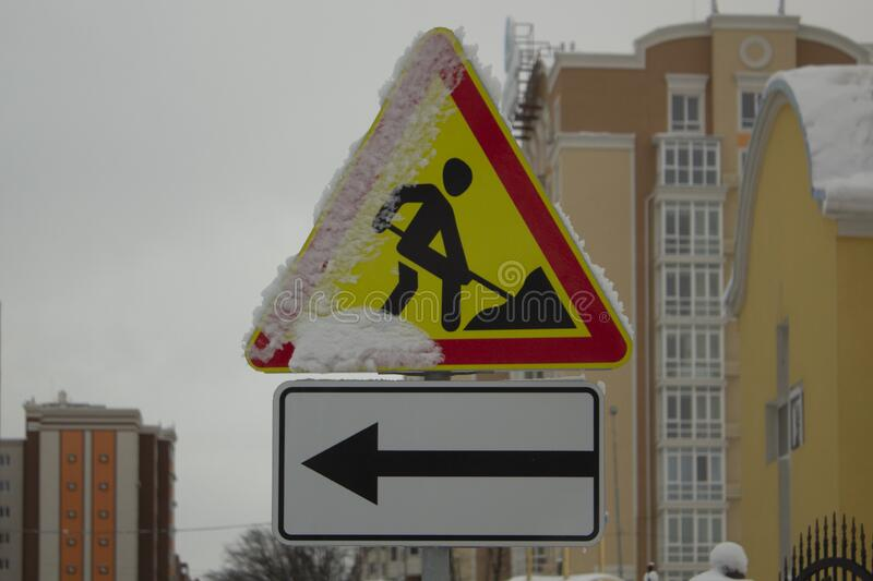 Roadwork road construction sign with snow on it. Road construction sign with snow on it. Winter roadworks stock image