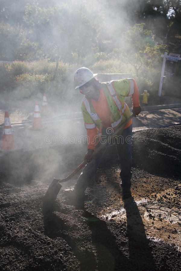 Roadworker repaves дорога с паром, приводом Encino, взглядом дуба, Калифорнией, США стоковое фото