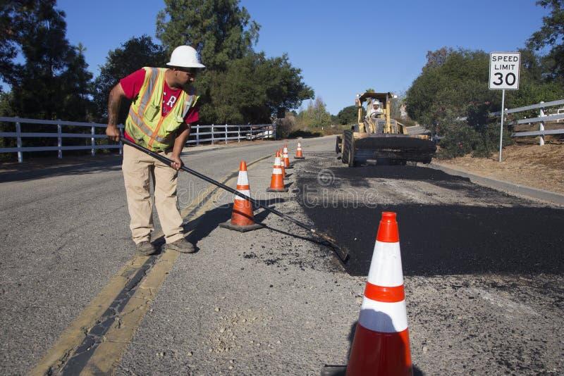 Roadworker repaves el camino con el vapor, impulsión de Encino, opinión del roble, California, los E.E.U.U. fotos de archivo