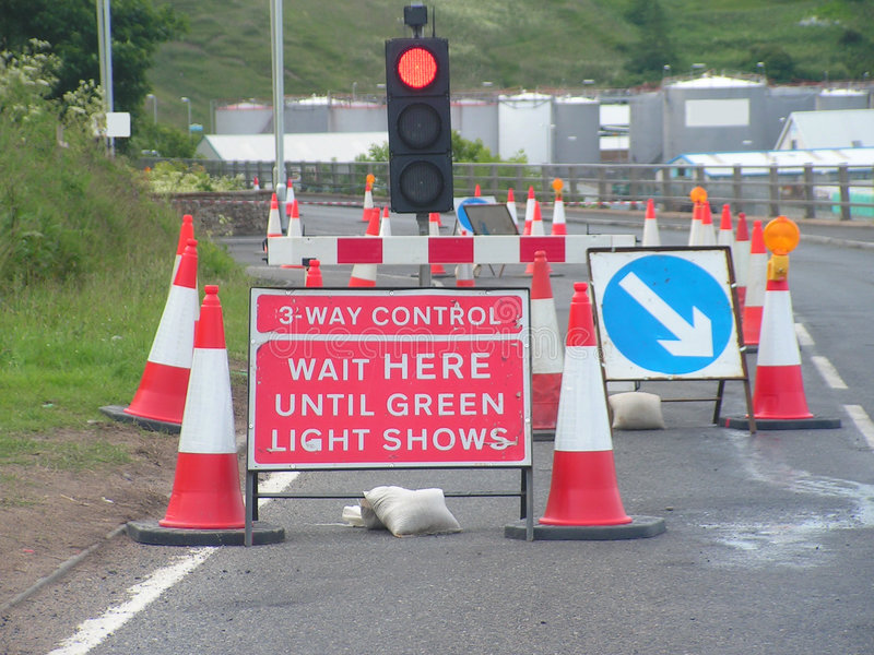 Roadworks. The start of a long set of road works with 3 way temporary traffic lights royalty free stock photo