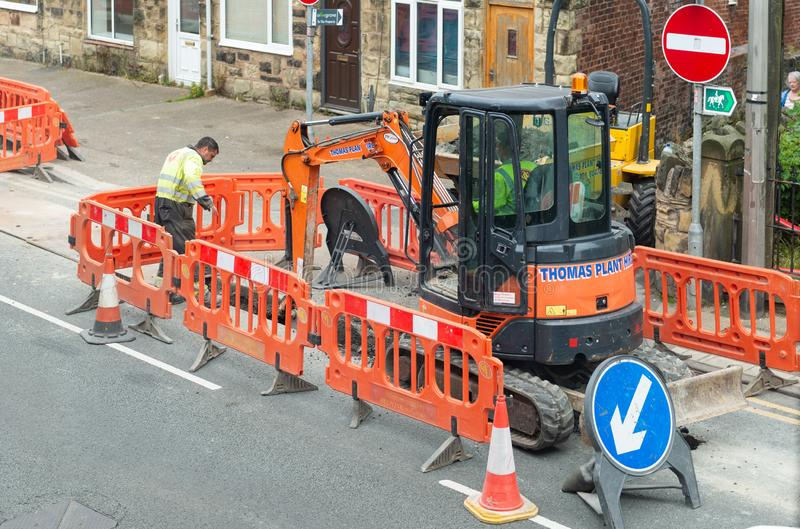 Roadworks in a street with digger, barriers and workmen. royalty free stock photo