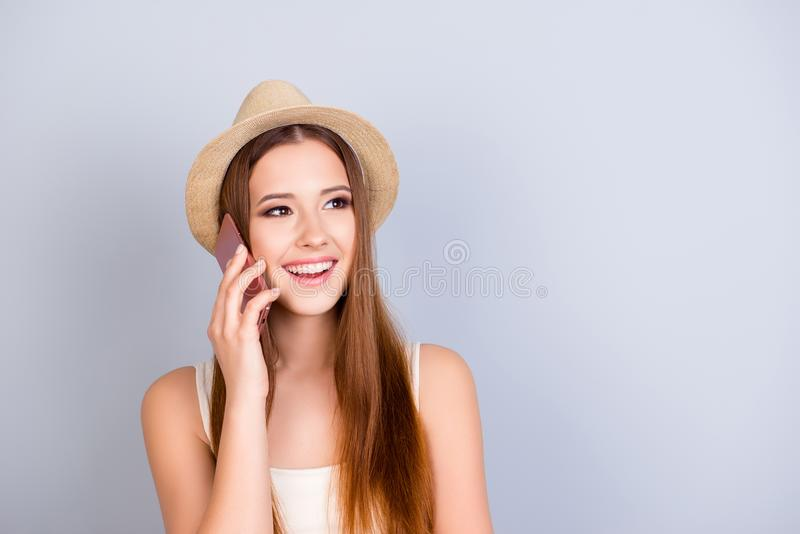 Roaming and communication concept. Young cute blond tourist in a. Hat is talking on her pda at the vacation. She is in casual light outfit on pure grey royalty free stock image