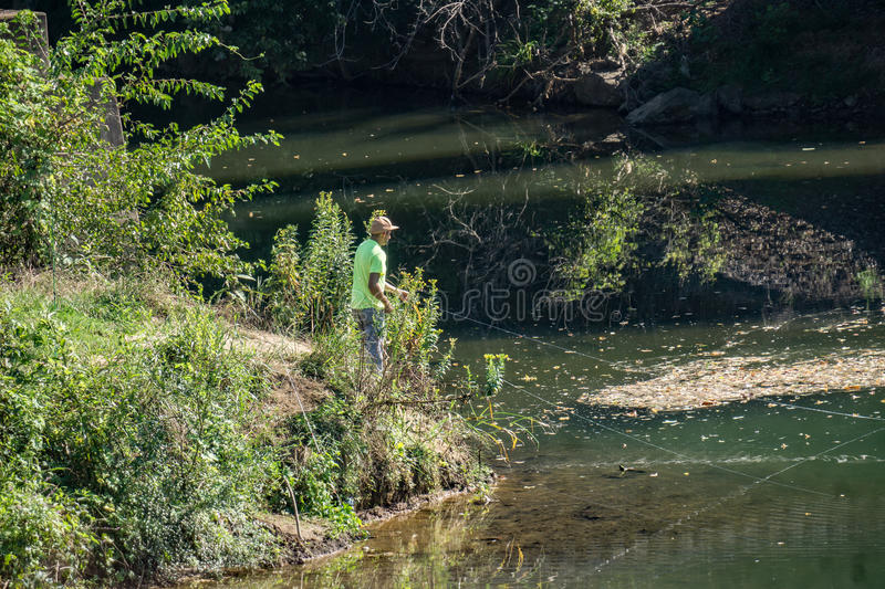 Fisherman on the Roanoke River. Roanoke County, VA – August 19th: A fisherman fishing for small mouth bass on the Roanoke River on a peaceful summer royalty free stock images