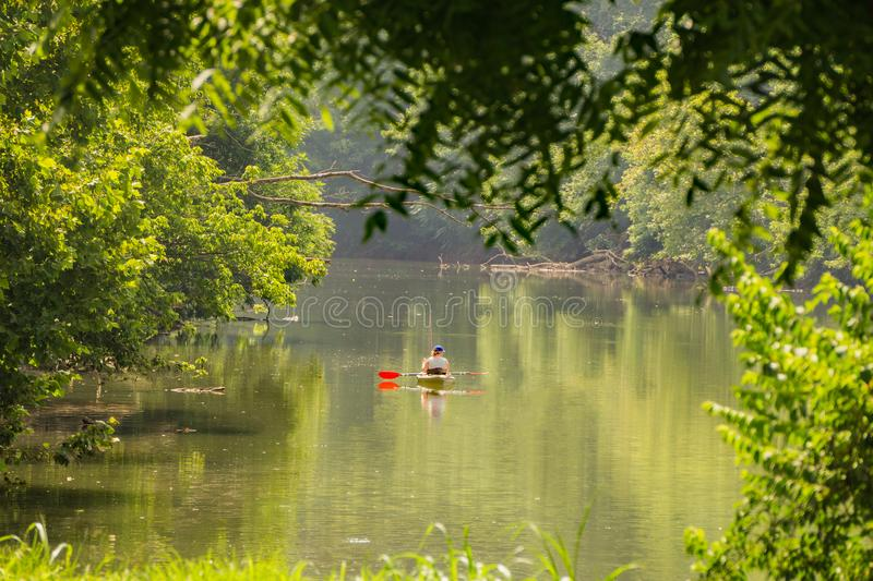 Woman Enjoying a Day of Fishing for Smallmouth Bass. Roanoke County, VA – June 30th: A female in kayaks enjoying fishing for smallmouth bass on the stock photos