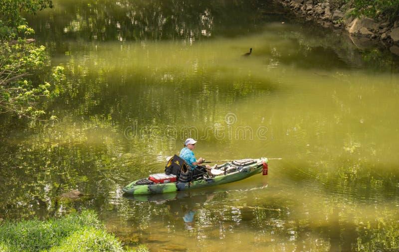 Fisherman Fishing For Smallmouth Bass. Roanoke County, VA – June 11th: Fisherman in kayaks fishing for smallmouth bass on the Roanoke River next to the royalty free stock photography
