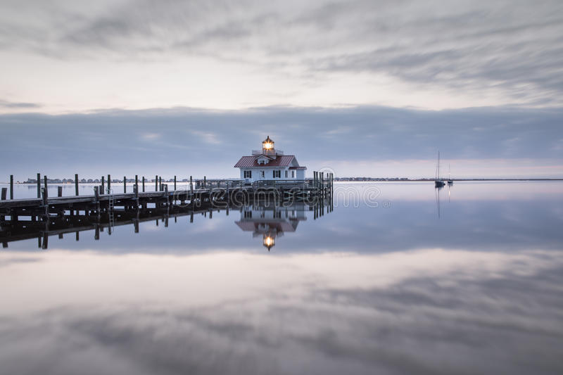 Roanoke Marshes Lighthouse Manteo North Carolina. The Roanoke Marshes Lighthouse reflecting in the water of Shallowbag Bay against the gray and blue sky of an stock photo