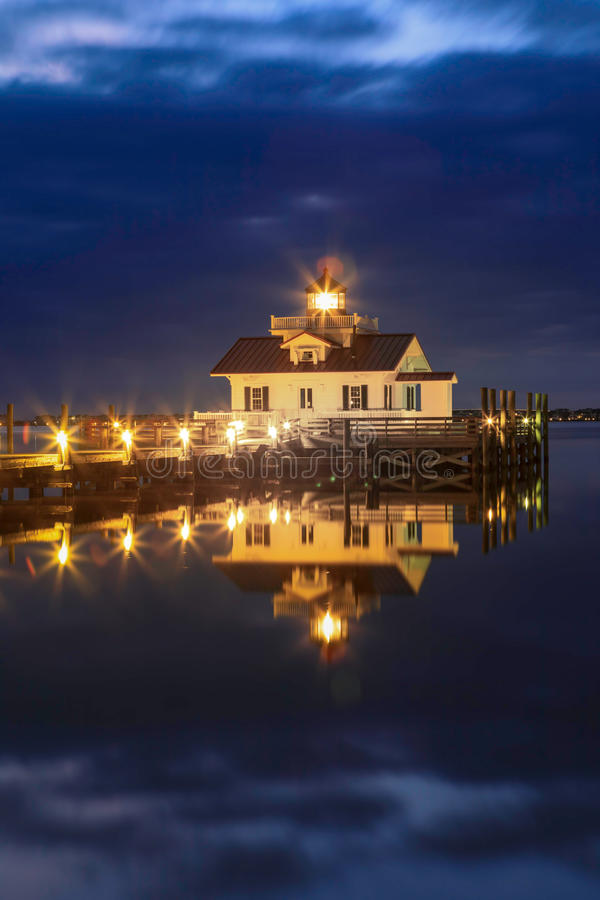 Roanoke Marshes Lighthouse Manteo North Carolina. Vertical image of the Roanoke Marshes Lighthouse illuminated and reflecting on the waters of Shallowbag Bay in royalty free stock images