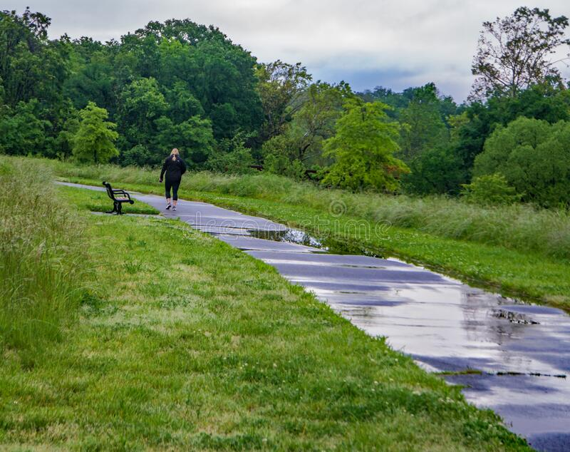 The Roanoke River Over It`s Banks by the Roanoke Valley Greenway. Walkers Enjoying a Beautiful Day on the Roanoke River Greenway stock image