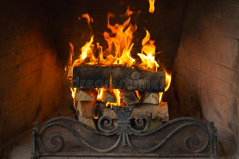 A roaring fire within a large stone arched fireplace. Horizontally framed shot royalty free stock photography