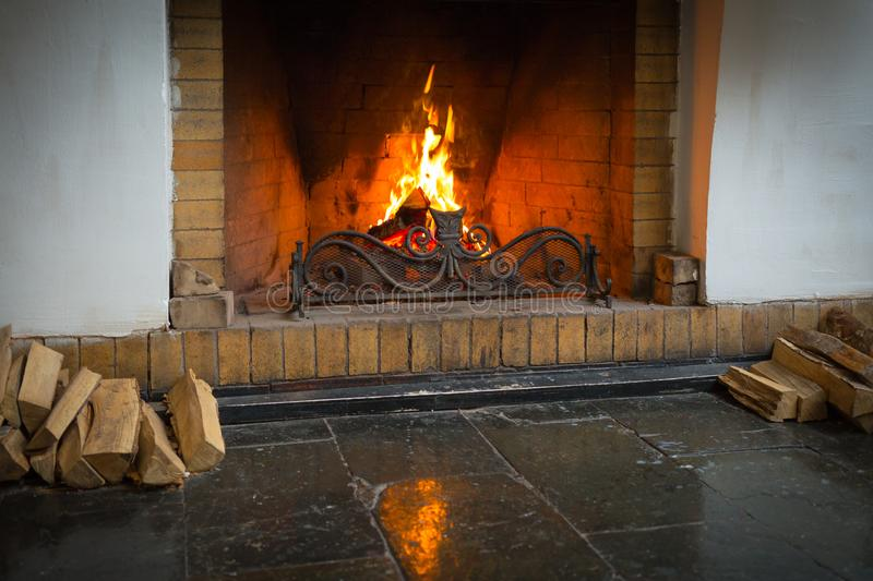 A roaring fire within a large stone arched fireplace, with pile of logs. stock photography