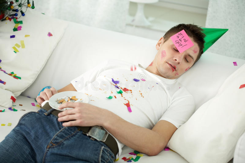 Roaring night. Young drunken man in party hat and with lipstick spots sleeping on sofa in confetti stock photos