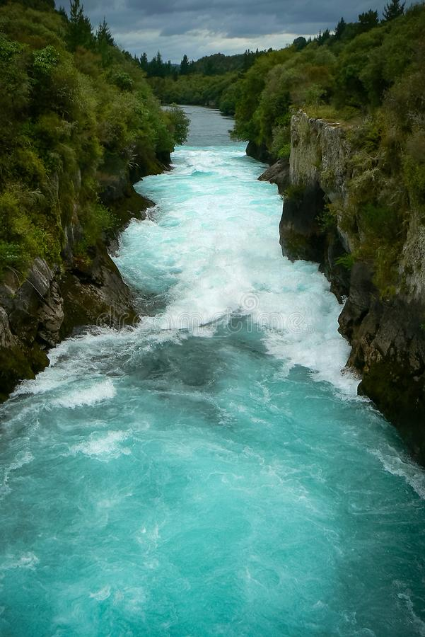 Turquoise water of the Waikato River at Huka Falls waterfall, North Island, New Zealand. Roaring turquoise water of the Waikato River coming from Lake Taupo at stock images