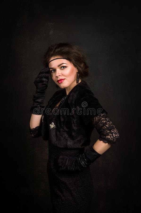 Roaring Twenties. Low key. A beautiful young woman in a black dress touches cheek with the hand on which she wears a black glove. royalty free stock images