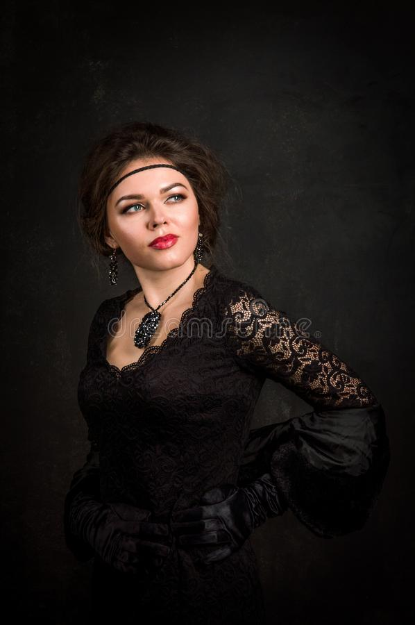 Roaring Twenties. Woman portrait in the style of Gatsby. Low key. Beautiful young woman in a black dress, satin gloves. stock photos