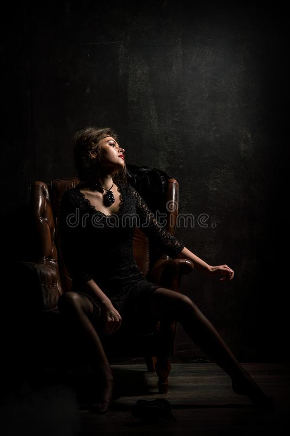 Roaring Twenties. Woman portrait in the style of Gatsby. Low key. A beautiful young woman in a black lace dress. royalty free stock images