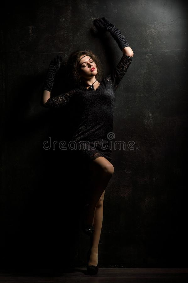 Roaring Twenties. Woman portrait in the style of Gatsby. Low key. Beautiful young woman in a lace black dress, posing sensually. royalty free stock images