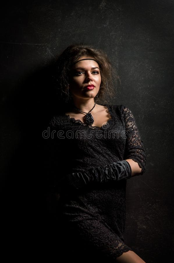 Roaring Twenties. Woman portrait in the style of Gatsby. Low key. Beautiful young woman in a lace black dress, posing sensually. stock photography