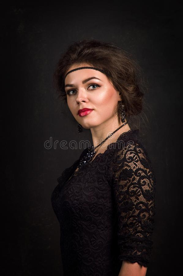 Roaring Twenties. Woman portrait in the style of Gatsby. Low key. Beautiful young woman in a black lace dress romantic looks. royalty free stock photography