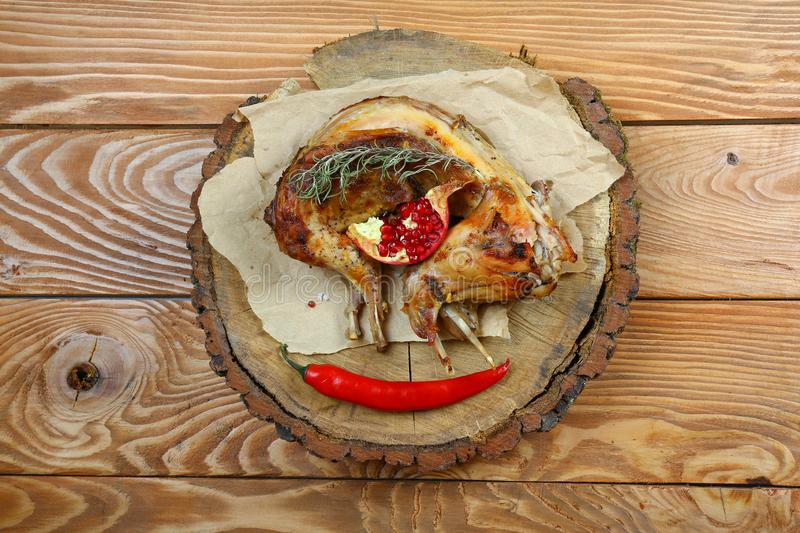 Roast baked whole rabbit on wooden board on paper. Ingredients for baked rabbit rosemary on rustic oak table. A festive meal. Top royalty free stock images