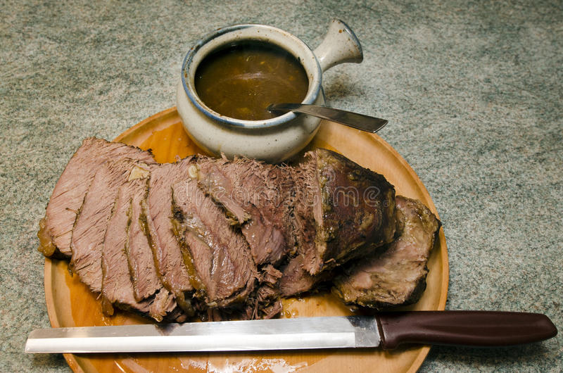 Roast beef. Cooked Roast beef on a cutting meat wooden board with roast beef slicing knife and gravy bowl stock photography