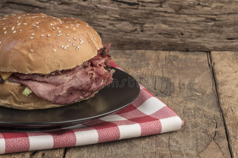 Roast beef burger on wooden table stock photography