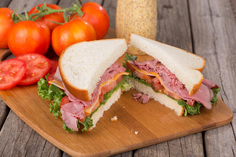 Roast Beef and Cheese Sandwich. Roast beef sandwich with lettuce, tomato and cheese on a cutting board royalty free stock photography