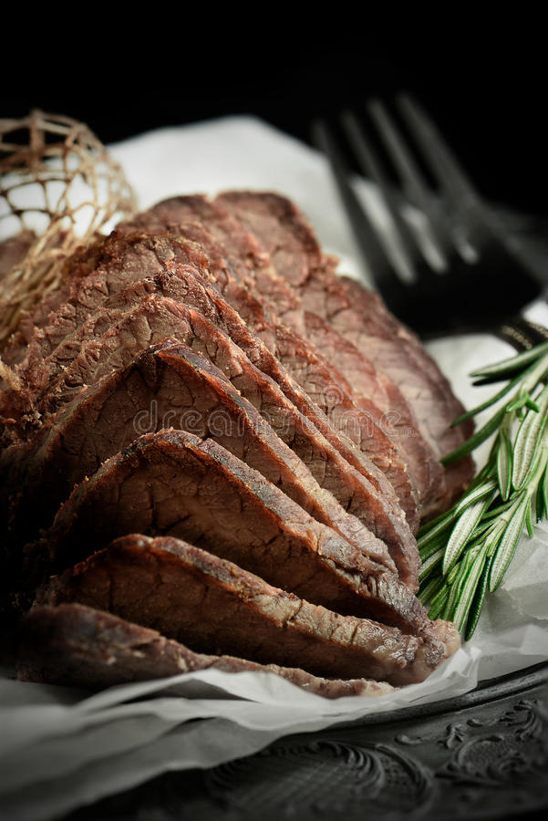 Roast Beef 6. A curated image of perfectly cooked prime topside roast beef, sliced and ready to eat against a dark, rustic background with copy space. Concept stock image
