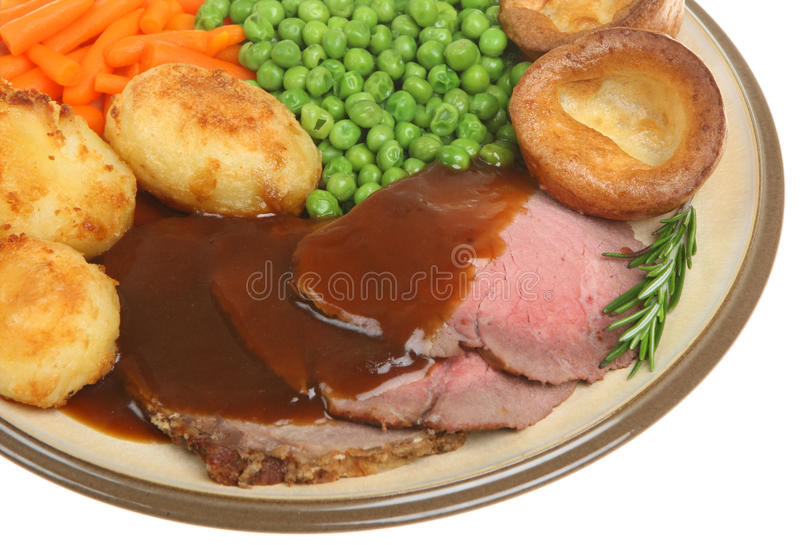 Roast Beef Dinner. Traditional roast beef dinner with Yorkshire pudding and gravy royalty free stock photos