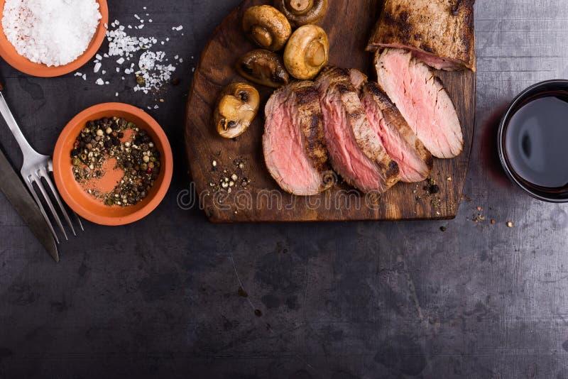 Roast beef steak with mushrooms. Roast beef fillet tenderloin with mushrooms on wooden cutting board royalty free stock photo