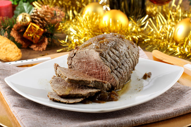 Roast beef with gravy. On Christmas background stock image