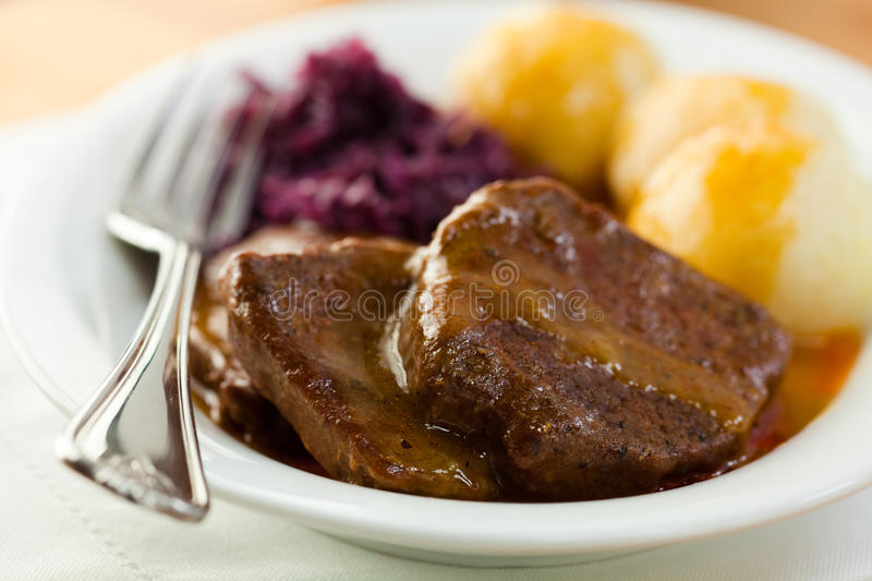Roast beef with potato dumplings and red cabbage. German cuisine stock photography