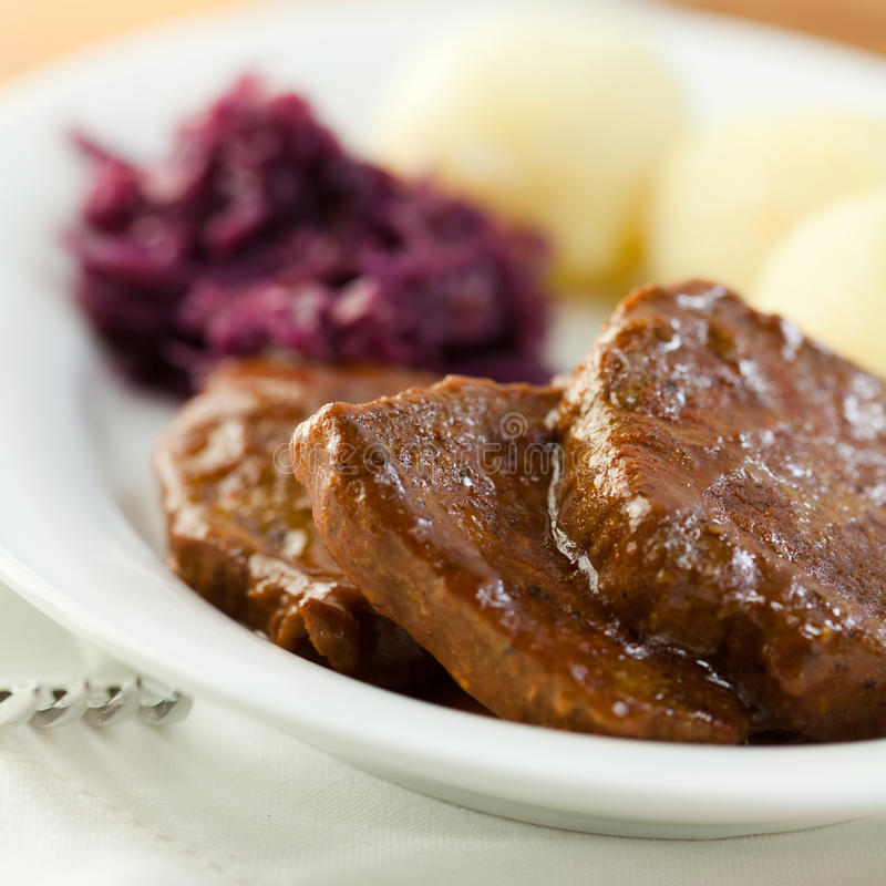 Roast beef with potato dumplings and red cabbage. German cuisine stock image