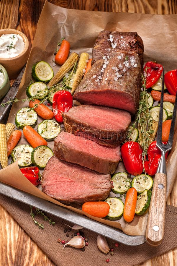 Roast beef. From tenderloin A large piece is cut into pieces. A large portion of meat with vegetables is served on a wooden board. Close up and vertical royalty free stock images