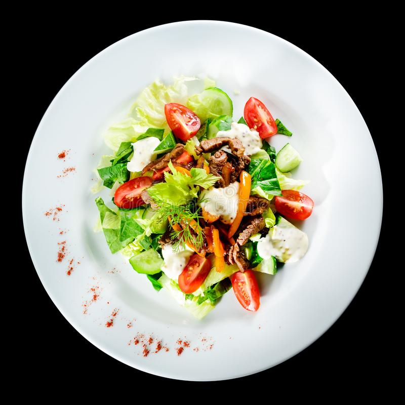 Roast beef salad with tomatoes, cucumbers, feta cheese and pepper in white plate isolated on black background. Food background, m stock photos