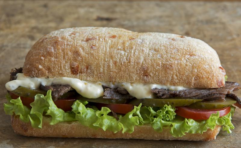 Roast beef sandwich with tomato salad and pickled cucumber stock photography