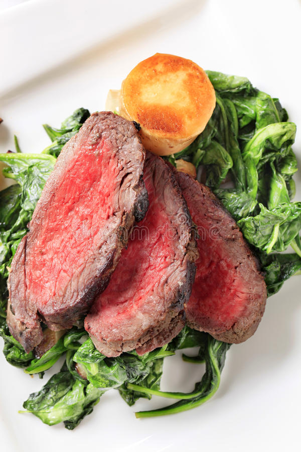 Roast beef with sauteed spinach stock photography