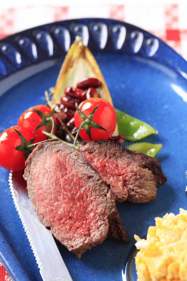 Roast beef, scrambled eggs and vegetables stock photo