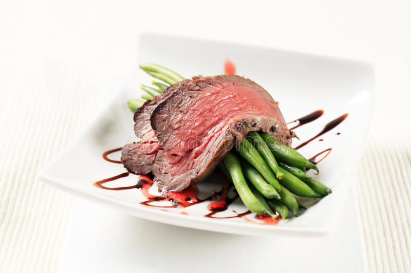 Roast beef and string beans stock photography