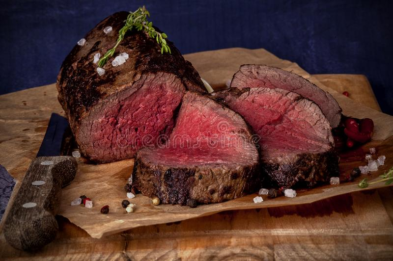 Roast beef. From tenderloin A large piece is cut into pieces. A large portion of meat served on a wooden board. Close up and horizontal orientation stock photo