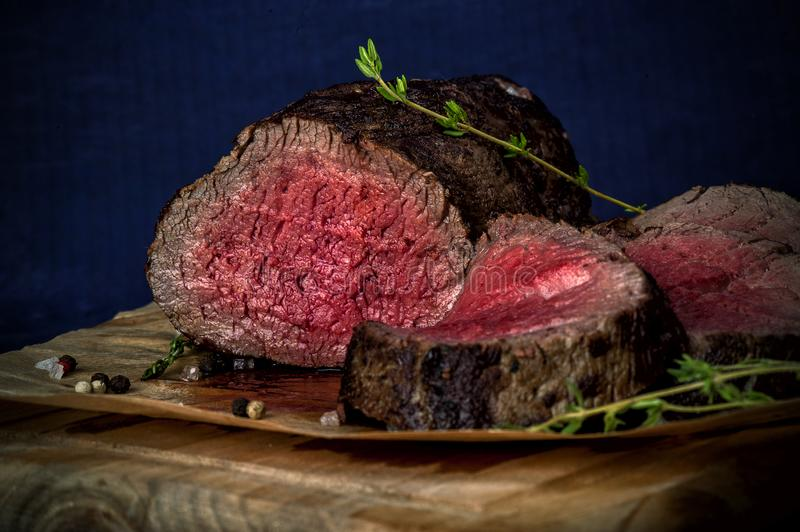 Roast beef. From tenderloin A large piece is cut into pieces. A large portion of meat served on a wooden board. Close up and horizontal orientation royalty free stock image