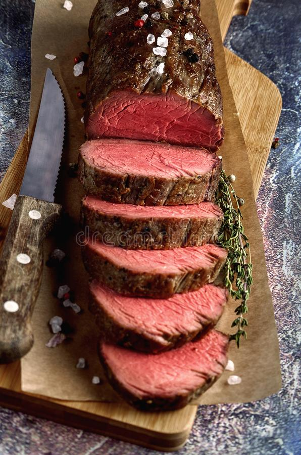 Roast beef. From tenderloin A large piece is cut into pieces. A large portion of meat served on a wooden board. Close up and vertical orientation stock photography