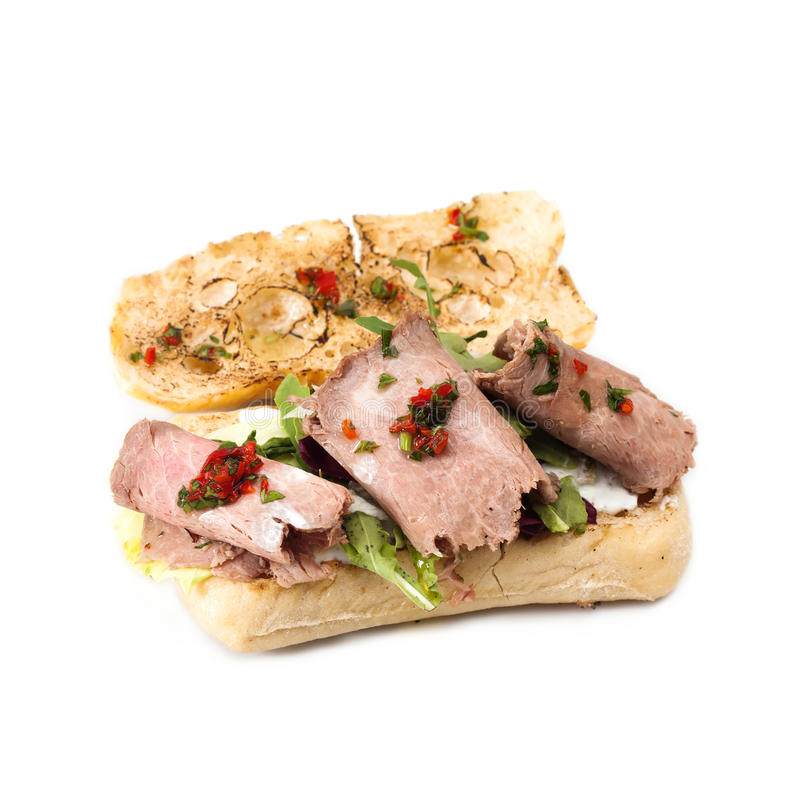 Roast beef toast with green salad. Classic sandwich grilled bread, baked meat fresh vegetables. White background royalty free stock images