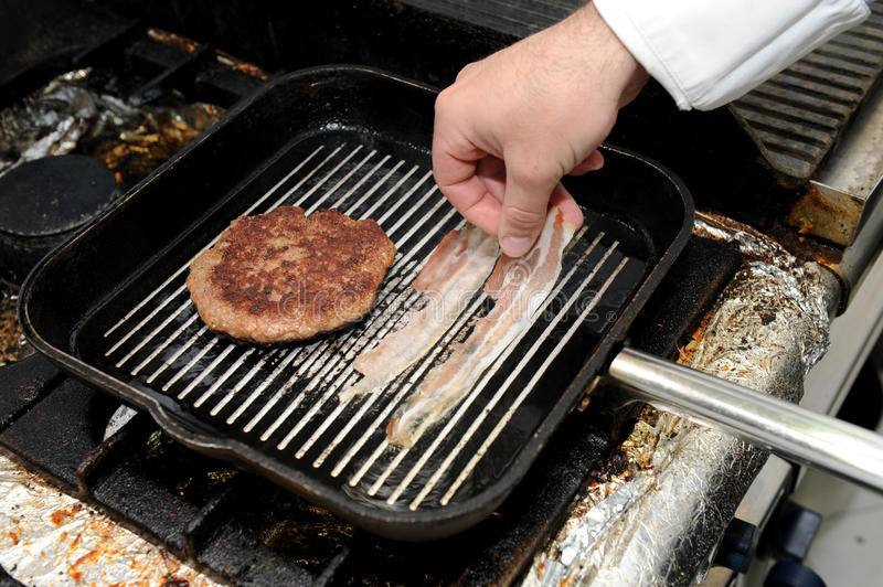 Roast burger and bacon on the grill pan. Cook is preparing hamburger and bacon. stock photo