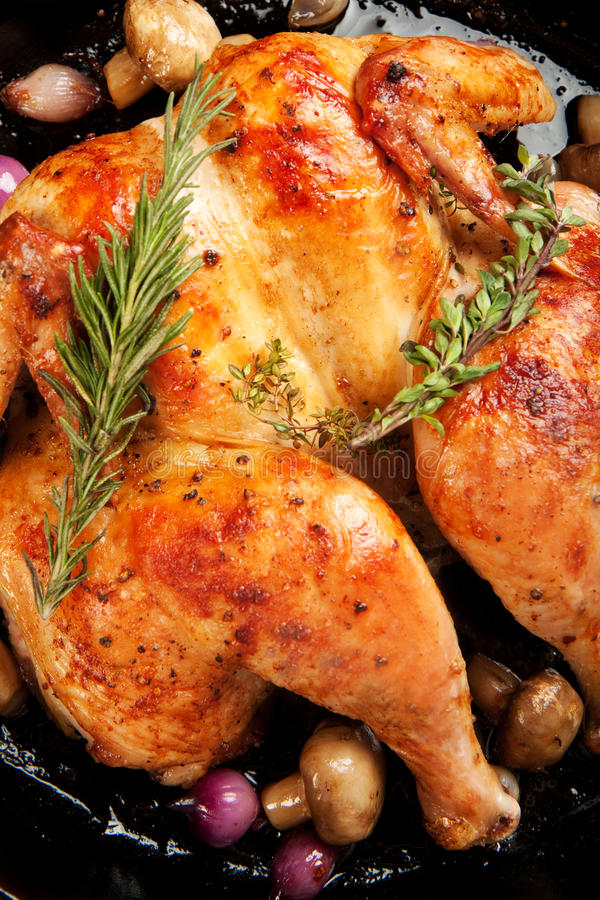 Roast Chicken. Whole chicken roasted in cast iron skilled with red pearl onions and mushrooms stock photo