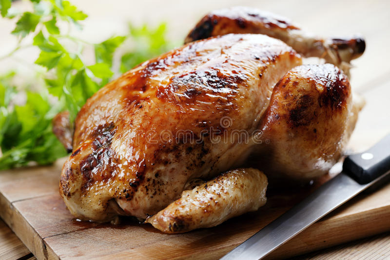 Roast chicken. Whole roasted chicken on a cutting board royalty free stock photos