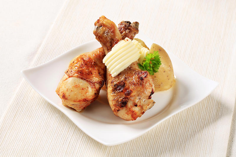 Roast chicken drumsticks and new potatoes royalty free stock photo