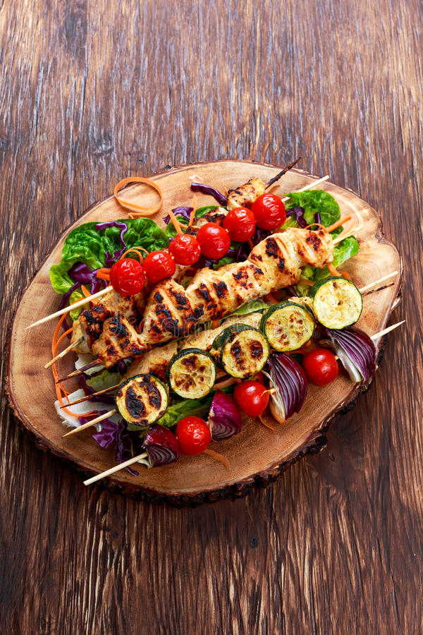 Roast Chicken filet kebab with cherry grilled on BBQ. tomatoes, zucchini and red onions on bamboo sticks royalty free stock photos